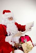 Santa Claus holding wish list in hands. Studio photo