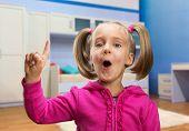 Little girl points her finger up
