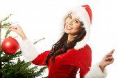 Smiling woman wearing santa claus decorating christmas tree.