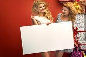 Two glamorous women holding sale board