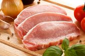 Raw pork chops on cutting board and vegetables on white background