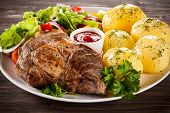 Barbecued steak, boiled potatoes and vegetable salad
