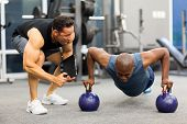 personal trainer motivates client doing push-ups in gym