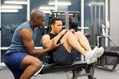 fit middle aged man with personal trainer in gym