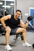 cheerful man lifting weights at gym