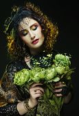 Young curly woman with bright visage holding big green flowers