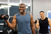 afro american muscle man holding dumbbell looking at the camera