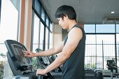 Man At The Gym Doing Set Up Treadmill For Fitness
