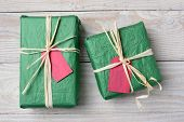 High angle image of two green Christmas presents on a rustic white wood table. Wrapped with crumpled tissue paper and tied with raffia both have blank red gift tags. Horizontal format.