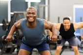 happy african man exercising in gym with dumbbells