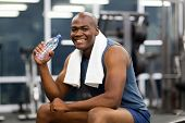 happy young african man drinking water after exercise