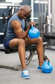sportive african man lifting kettle bell in gym
