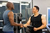 friendly middle aged gym trainer greeting client