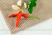 Two Chili Peppers,garlic And Lime Leaves On A Napkin