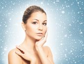 Face of young and healthy girl over winter background with a snowflakes