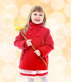 Little girl in a red coat and holding flowers.