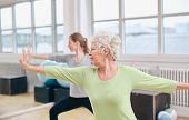 picture of gym workout  - Two women doing stretching and yoga workout at gym - JPG