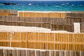 Sand beach of Tarifa with wooden sand-fences against blue sky and aquamarine sea
