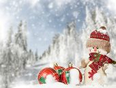 Red Christmas balls and snowman in the snow, , snow cowered pine trees in the background