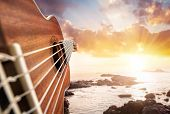 image of guitar  - Guitar player at seascape sunset cloudy sky background - JPG