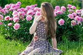 Nice Young Woman In The Park Near Peonies
