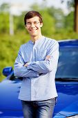 Handsome smiling guy wearing glasses standing in front of car with crossed arms