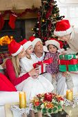 Family wearing christmas hat while holding presents at home in the living room