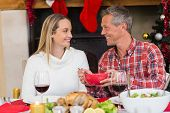 Man serving wife during the dinner at home in the living room