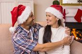 Festive couple in santa hat hugging on the couch at home in the living room