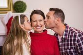 Daughter with her father kissing her mother at home in the living room