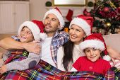 Happy family in santa hat hugging under the cover at home in the living room