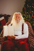 Portrait of santa showing his book at home in the living room