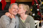 Mature woman kissing the cheek of her husband at home in the living room