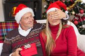 Man covering partner eyes and offering a gift to her at home in the living room