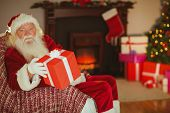Cheerful santa claus offering a gift at home in the living room