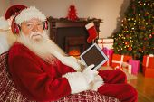 Santa claus listening music and using tablet at home in the living room