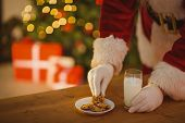 Santa picking cookie and glass of milk on the table at home