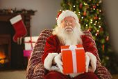Santa claus offering a red gift at home in the living room