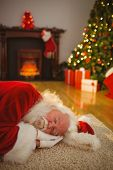 Santa claus napping on the rug at home in the living room