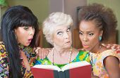 stock photo of tawdry  - Trio of cute mature women reading a book - JPG