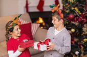 Brother and sister in headband holding present at home in the living room