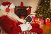 Santa listening music and touching tablet at home in the living room