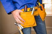 Close up of handyman in tool belt in a new house