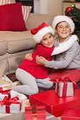 Brother and sister hugging near gifts at home in the living room