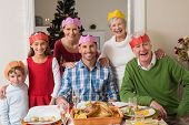 Happy extended family in party hat at dinner table at home in the living room
