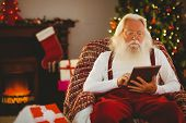Santa claus using tablet on the armchair at home in the living room