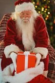 Portrait of santa stocking gifts in his sack at home in the living room