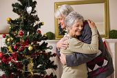 Senior couple hugging beside their christmas tree at home in the living room
