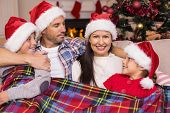 Festive family in santa hat hugging under the cover at home in the living room
