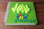Concept of conservation forests of cut paper on notebook on wooden table